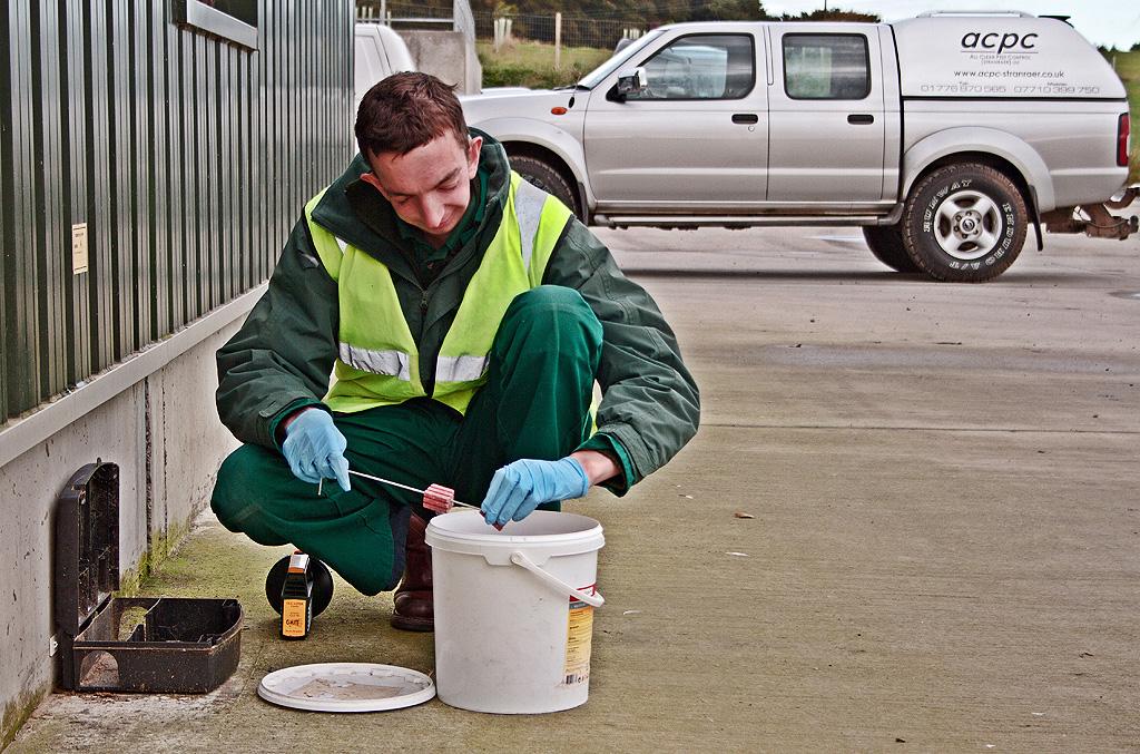 ACPC Technician servicing a perimiter bait box.
